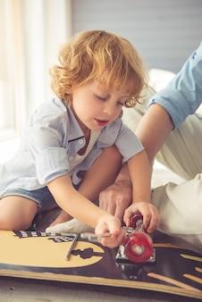 Un mignon petit garçon répare une planche à roulettes.
