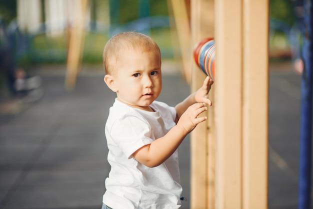 Mignon petit garçon s'amusant sur une aire de jeux