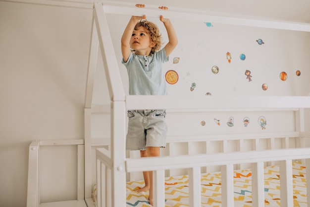 Mignon petit garçon s'amusant au lit en forme de maison