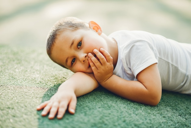 Mignon petit garçon s'amuse sur une aire de jeux