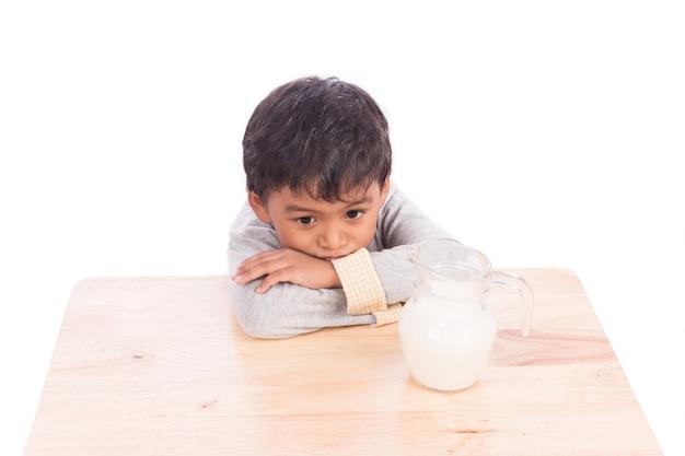 Mignon petit garçon s'ennuie avec du lait