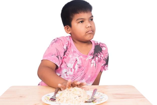 Mignon petit garçon s'ennuie avec de la nourriture