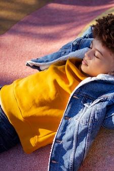 Mignon petit garçon se détendre sur l'aire de jeux