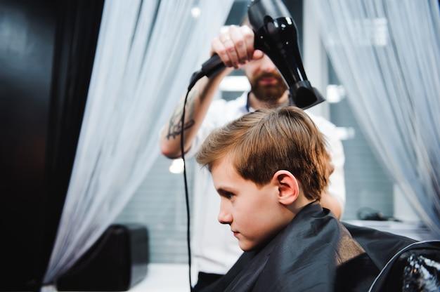 Mignon petit garçon se fait couper les cheveux par un coiffeur au salon de coiffure