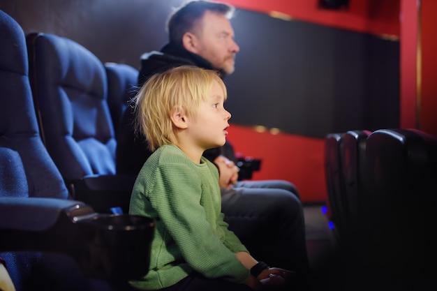 Mignon petit garçon avec son père en regardant un film de dessin animé au cinéma