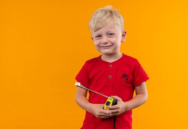 Un mignon petit garçon souriant aux cheveux blonds et aux yeux bleus portant un t-shirt rouge tenant un mètre ruban à mesurer sur un mur jaune