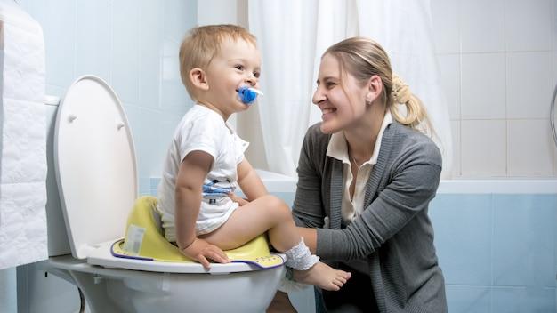 Mignon petit garçon souriant à sa mère assis sur le siège des toilettes.