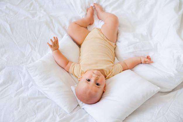 Mignon petit garçon souriant se trouve dans le lit de la maison. literie pour enfants