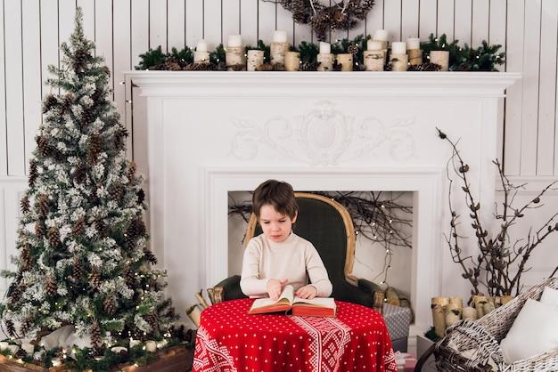 Mignon petit garçon à une table à noël