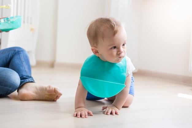 Mignon petit garçon en tablier rampant sur le sol pendant que sa mère essaie de le nourrir