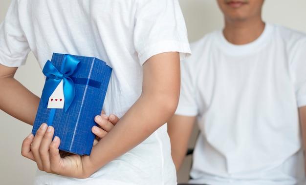 Mignon petit garçon tenant un cadeau pour le père derrière son dos, gros plan