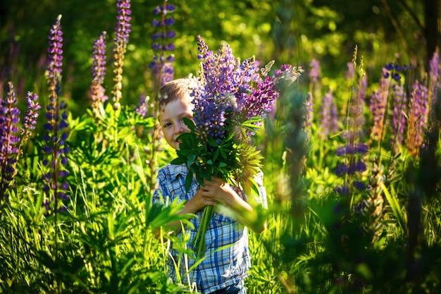 Mignon petit garçon, tenant des fleurs au printemps ensoleillé
