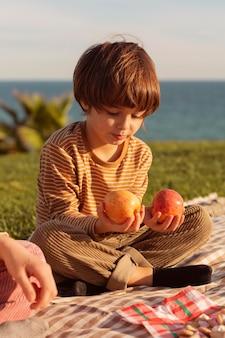 Mignon petit garçon tenant des pommes