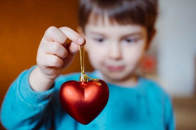 Mignon petit garçon tenant avec un sourire joyeux un coeur en forme de rouge sur son salon