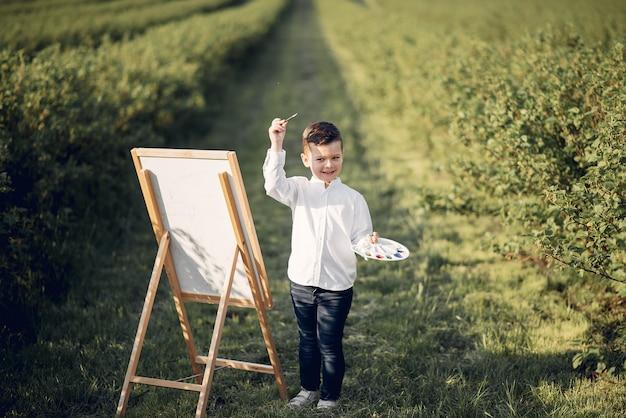 Mignon petit garçon en train de peindre dans un parc