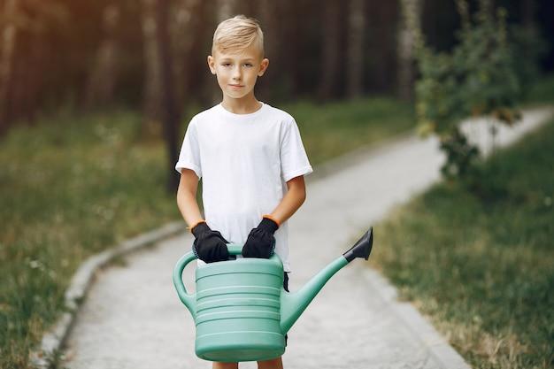 Mignon petit garçon en train de planter un arbre dans un parc