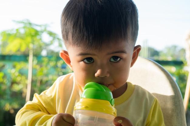Mignon petit garçon en train de sucer de l'eau des bouteilles