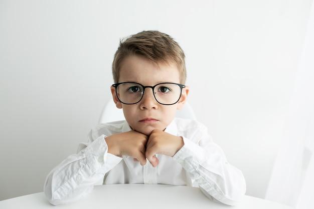 Mignon petit garçon utilisant un ordinateur portable tout en faisant ses devoirs contre blanc