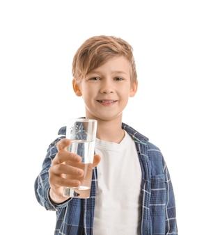 Mignon petit garçon avec un verre d'eau sur blanc