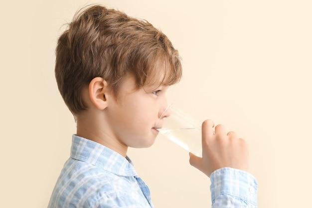 Mignon petit garçon avec un verre d'eau sur la couleur