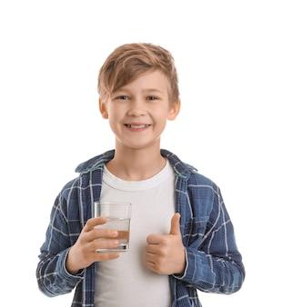 Mignon petit garçon avec un verre d'eau montrant le pouce vers le haut sur blanc