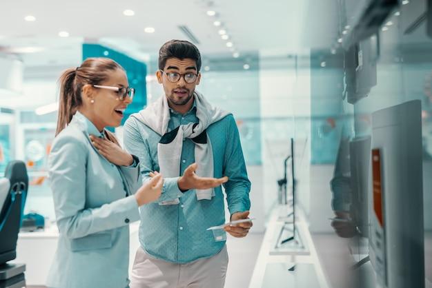 Mignon séduisant jeune couple multiculturel habillé élégant en choisissant un nouveau téléviseur plasma dans un magasin de technologie. homme montrant à la télévision pendant que la femme le regarde.