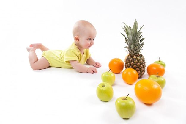 Mignon souriant enfant en bonne santé se trouve sur blanc entre frui