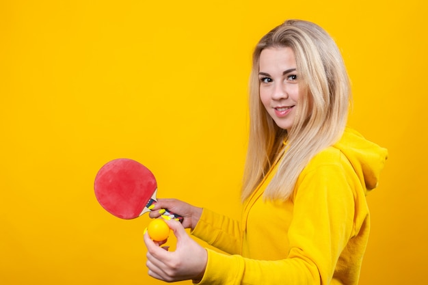 Mignonne belle jeune femme blonde dans des vêtements sportifs décontractés jaunes jouer au ping-pong, tenant une balle et une raquette.