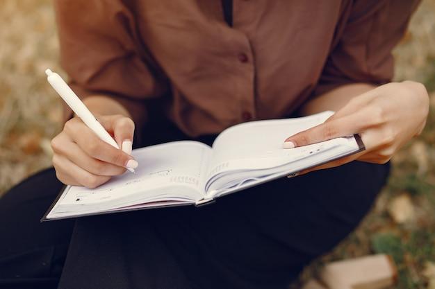 Mignonne étudiante travaillant dans un parc et utilisant le cahier
