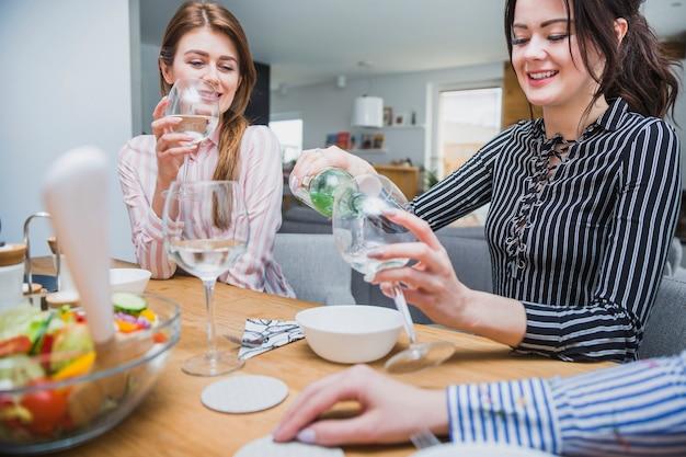 Mignonne femelle verser du vin blanc pour un ami