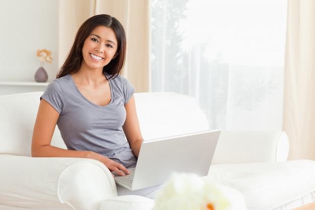 Mignonne femme assise sur le canapé avec ordinateur portable à la recherche dans la caméra
