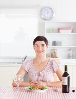 Mignonne femme assise à une table avec du vin pour le déjeuner