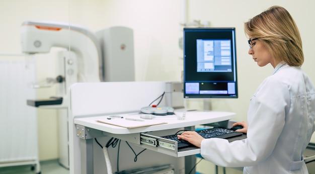 Mignonne femme médecin professionnelle travaille avec une machine moderne de système de mammographie x-ray dans un hôpital ou une clinique privée.