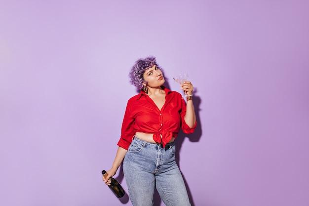 Mignonne femme merveilleuse en chemise élégante rouge détient verre et bouteille de vin blanc et sur lilas.