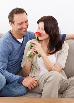 Mignonne femme sentant une rose rouge tout en vous relaxant sur le canapé