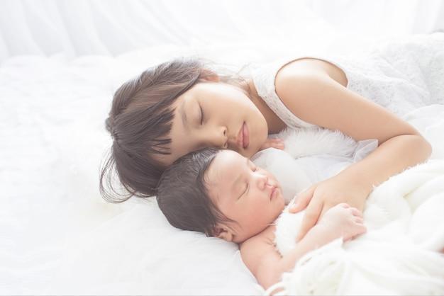 Mignonne grande soeur avec nouveau bébé nouveau-né