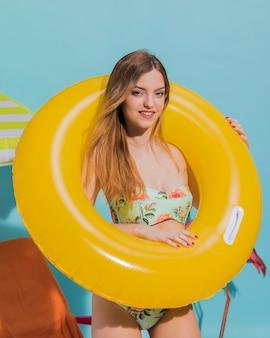 Mignonne jeune femme debout dans un cercle de nage en studio