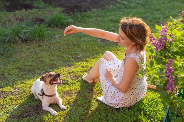 Mignonne jeune femme mince joue avec son chien drôle bien-aimé dans la cour par une journée d'été ensoleillée. beau