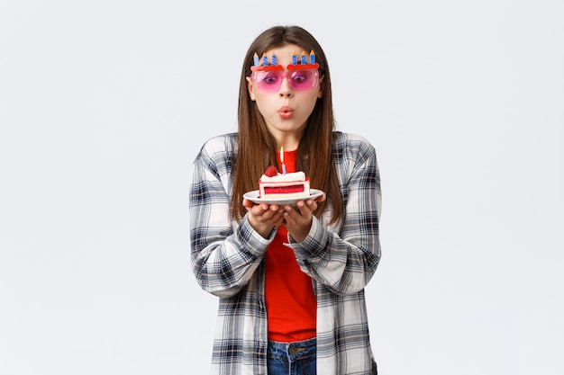 Mignonne jeune fille tendre b-day dans des verres, soufflant une bougie allumée sur le gâteau d'anniversaire, faisant souhait et célébrant à la fête, fond blanc