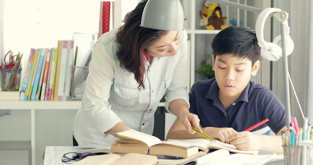 Mignonne mère asiatique aidant votre fils à faire vos devoirs.