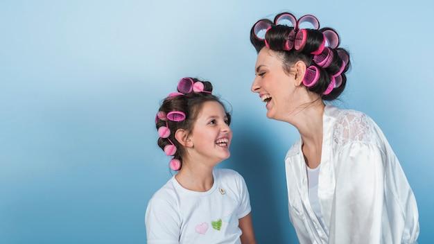 Mignonne mère et fille en bigoudis en riant