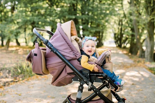 Mignonne petite belle petite fille assise dans le landau ou la poussette et attendant maman. enfant souriant heureux aux yeux bleus.