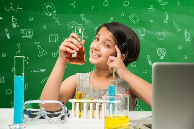 Mignonne petite écolière asiatique indienne expérimentant ou étudiant la science en laboratoire, sur fond de tableau vert avec des griffonnages éducatifs