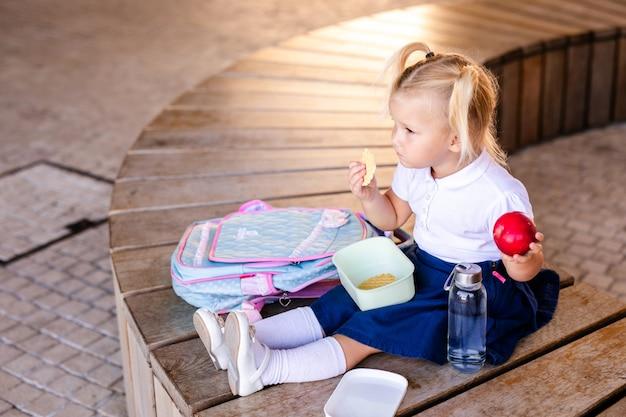 Mignonne petite écolière souriante tenant un hamburger et du jus d'orange en plein air