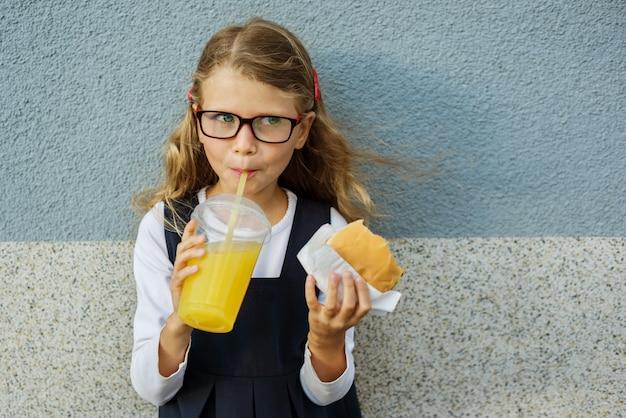 Mignonne petite écolière souriante tenant un hamburger et du jus d'orange