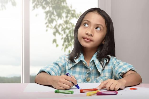 Mignonne petite enfant asiatique dessinant avec un crayon coloré