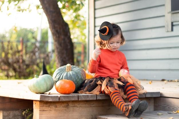 Une mignonne petite fille 2-3 dans un costume de sorcière orange et noir est assise à côté de citrouilles sur la terrasse d'une maison grise en bois
