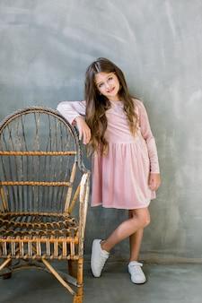 Mignonne petite fille de 5-6 ans portant une robe rose élégante sur fond gris. regardant la caméra. fête d'anniversaire. fête.