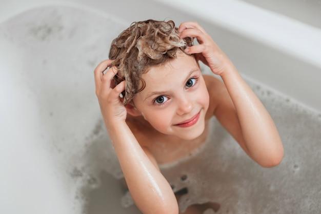 Mignonne petite fille de 6 ans se lave la tête, la tête en mousse