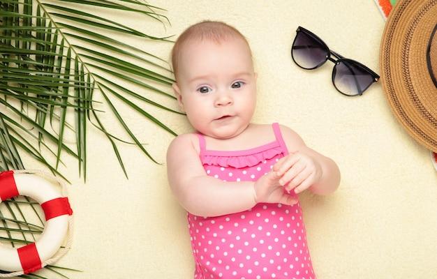 Mignonne petite fille avec des accessoires de plage sur la lumière. vacances en mer avec bébé, concept d'été